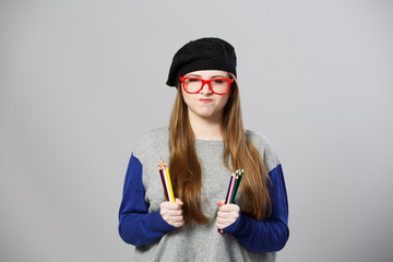 Cute girl at beret holds pencils