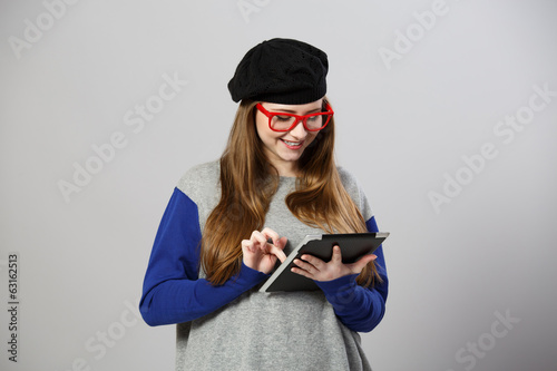 Girl at glasses and beret works with tablet pc