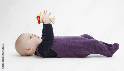 baby lying on his back with toy