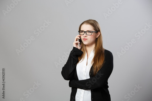 Business woman speaks by phone indignantly