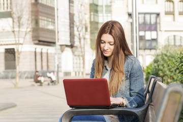 Young woman laptop computer in the street.