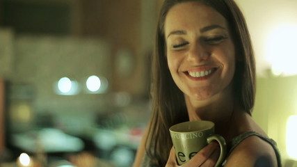Woman drinking coffee and smiling to camera