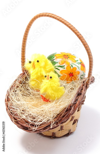Easter chickens in wicker basket and painted egg