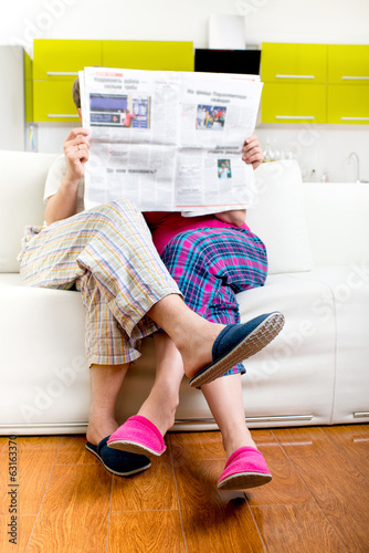 Married couple reading newspaper dressed in pajamas sitting in s