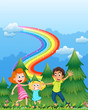 A happy family near the pine trees with a rainbow in the sky