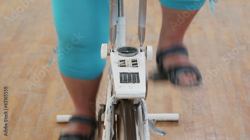 overweight woman exercising legs on bike simulator