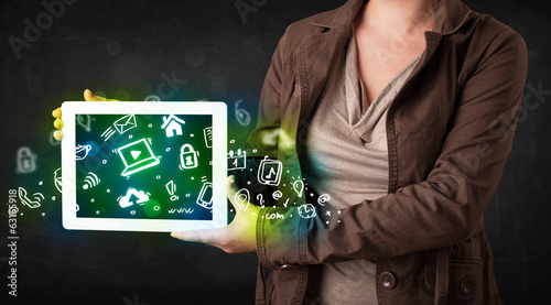 Leinwandbild Motiv Person holding tablet with green media icons and symbols