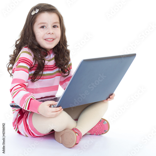 little girl sitting on the floor with a laptop.