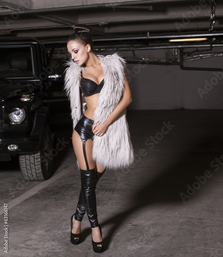 sexy woman in lingerie and fur coat posing beside a car