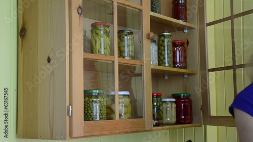 Girl put pickled olives and peppers glass jar preserves to shelf