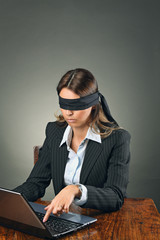 Blindfolded business woman with laptop