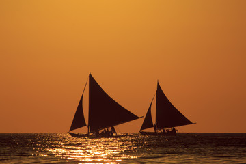Sunset cruise on traditional island sailboats