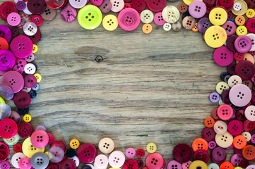 sewing buttons on wood background