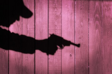 Human silhouette with handgun in shadow on wood background, XXXL