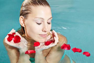Frau im Schwimmbad im Wellnesshotel mit Rosenblättern