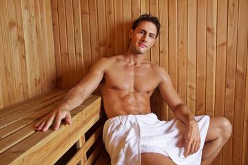 Attraktiver Mann sitzt in Sauna vom Hotel