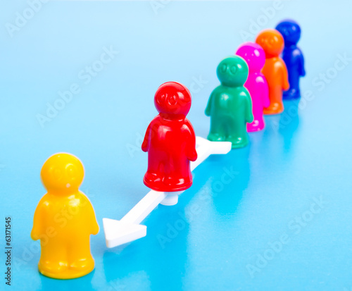 group of toy people and direction arrow