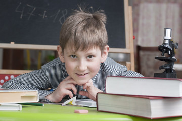 Smiling boy with school books on the table