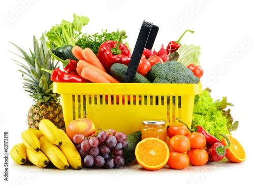 Plastic shopping basket with groceries isolated on white