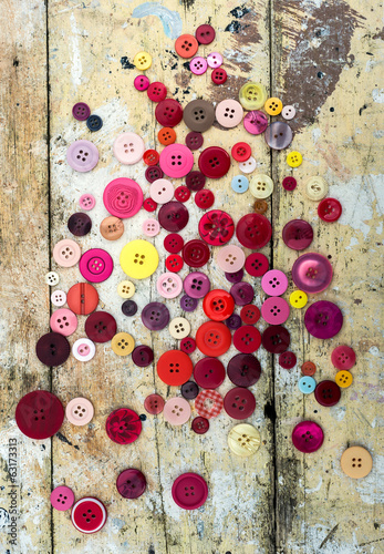 sewing buttons on grungy wood background