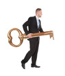 Businessman carrying an old-fashioned large brass key