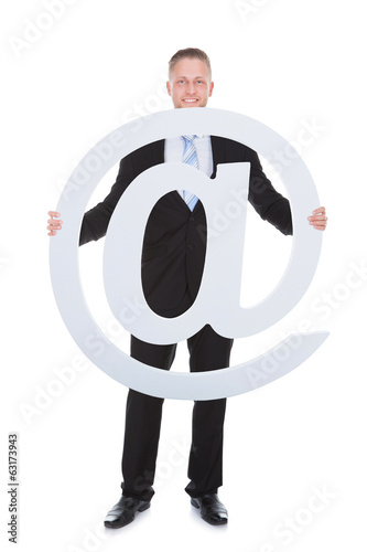 Businessman holding an - At - sign or internet icon