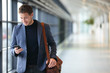 Leinwanddruck Bild - Man on smart phone - young business man in airport