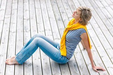 Woman sitting with closed eyes on wooden floor