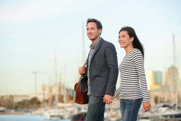 Young couple walking outdoors in city harbor