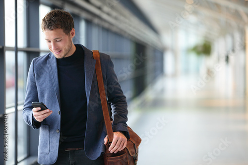Leinwanddruck Bild Man on smart phone - young business man in airport
