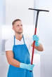 canvas print picture - Male janitor using a squeegee to clean a window