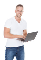Smiling man in jeans standing using a handheld laptop computer