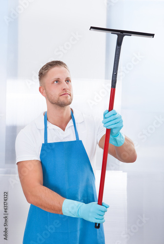 canvas print picture Male janitor using a squeegee to clean a window