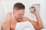 Man screaming in frustration at his alarm clock