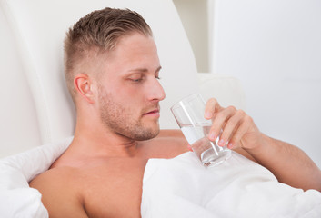Man drinking a glass of water in bed