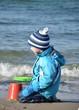 Kind spielt am Meer in wasserfester Kleidung