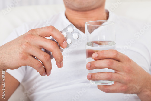 Man With Pack Of Pills And Water Glass