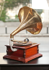 Golden and red gramophone isolated on wooden table