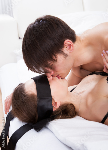 Man Kissing Sexy Blindfolded Woman In Bed