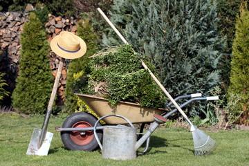 Gärtnerwerkzeug, Schubkarre etc. steht im Garten