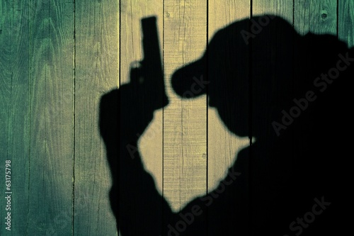 Secret service agent in  silhouette on natural wooden background