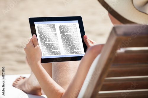 Woman Reading eBook On Beach Chair