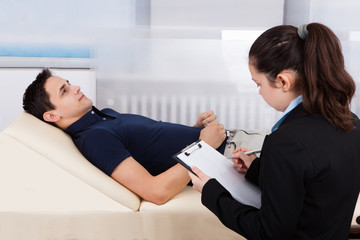 Psychologist Writing Notes While Patient Lying On Bed