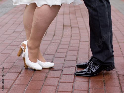 Shoes of a bride and groom walking by the pavement city