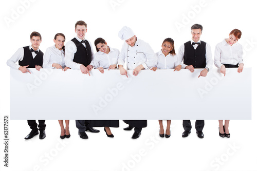 Group of catering staff holding a blank banner - 63177573