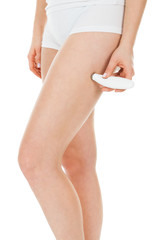 Woman Applying Microdermabrasion On Thigh