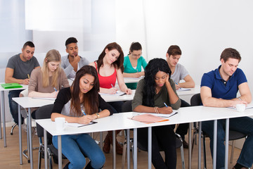 College Students Writing At Desk