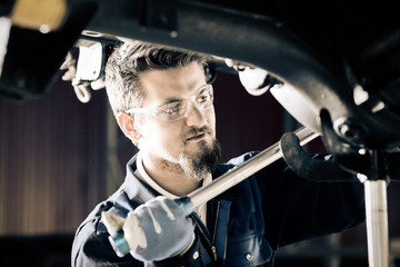 Handsome car mechanic at work