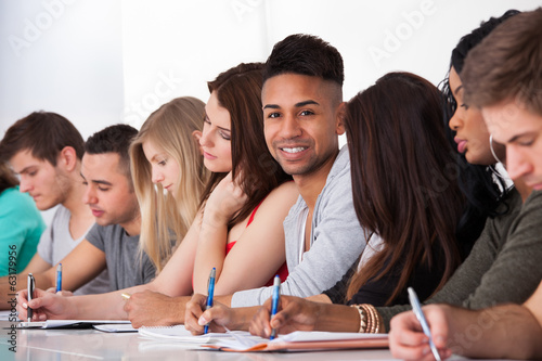 Confident Student Sitting With Classmates Writing At Desk