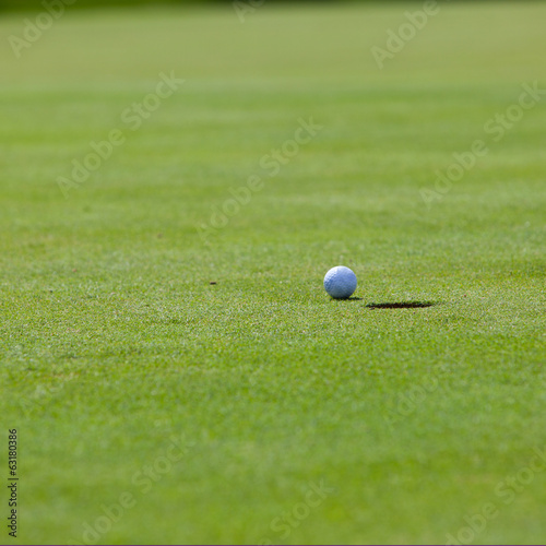 Golf ball lying on the lip of the cup at the hole